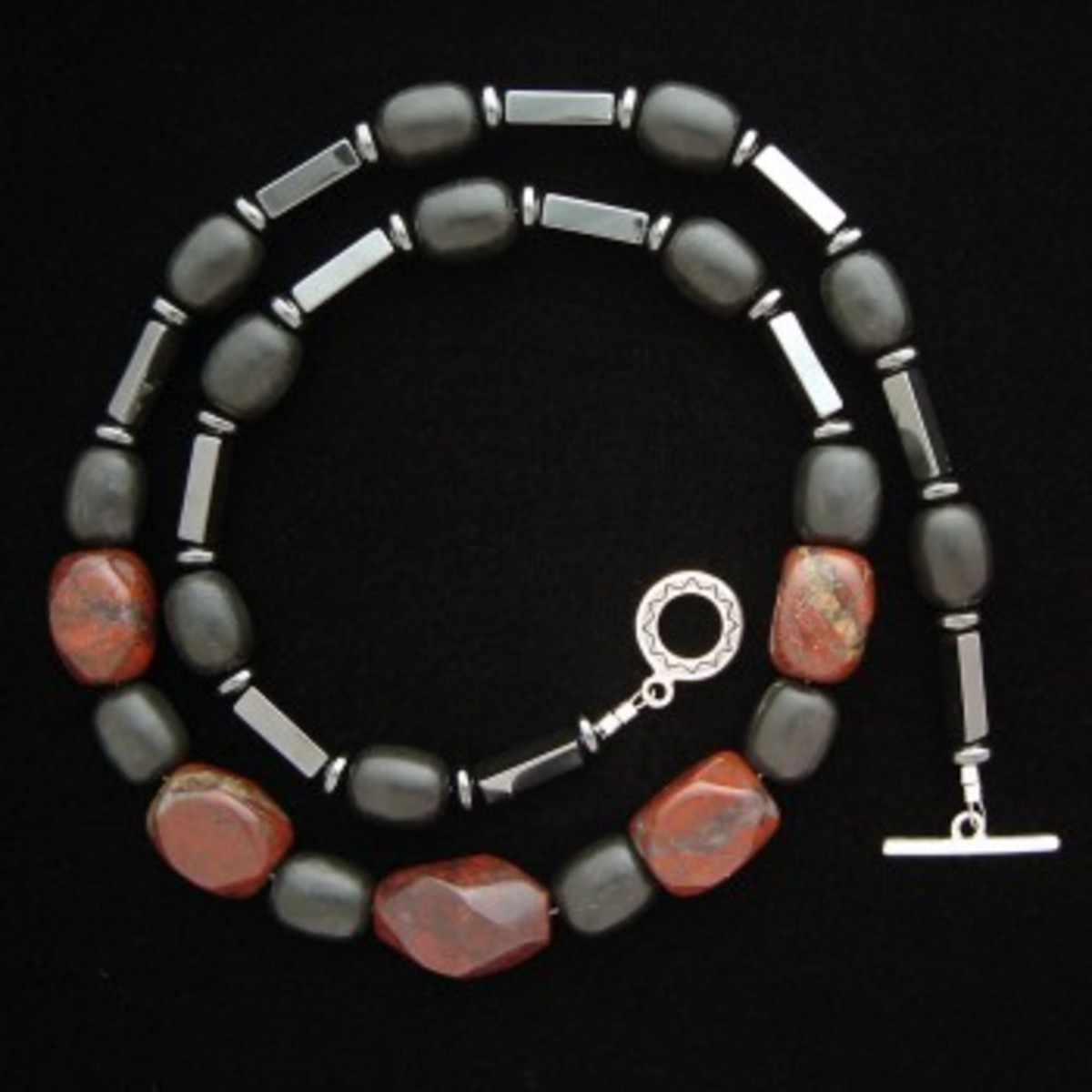 Poppy jasper, hematite, and onyx necklace coiled neatly to fit into a smaller image frame.