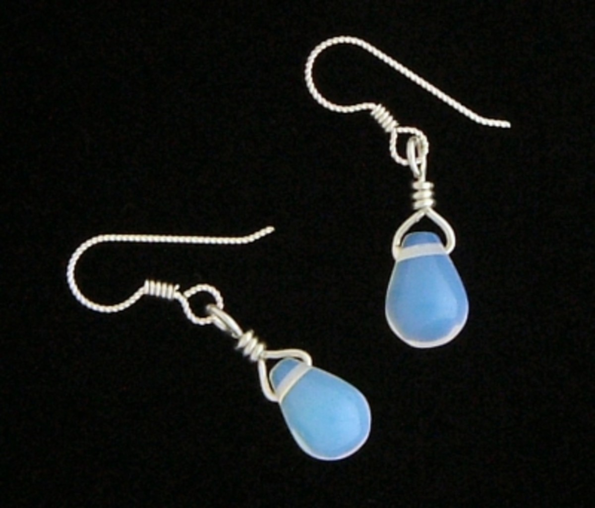Sea opal glass and sterling silver earrings, with black velvet background.