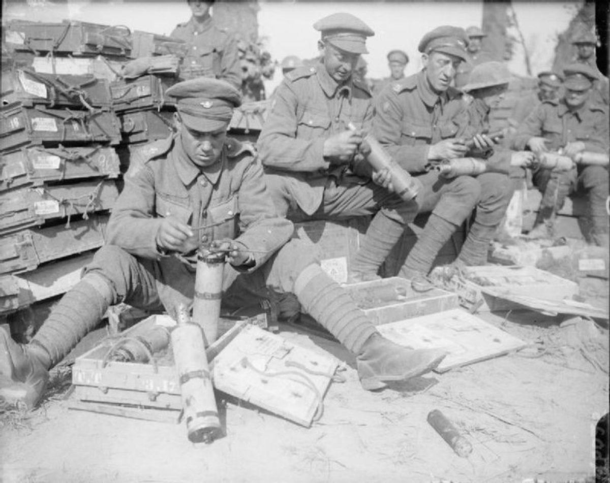As part of their daily routine, these men are adding fuses to shells.
