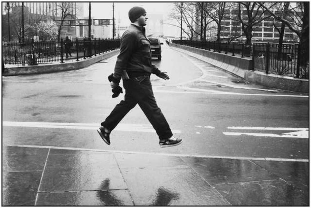 Man levitating while walking across street.