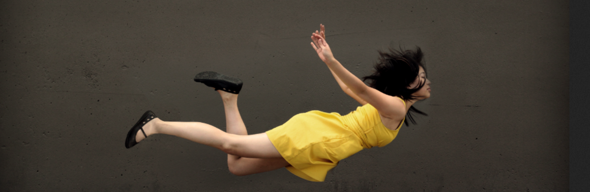 Asian girl levitating in yellow dress