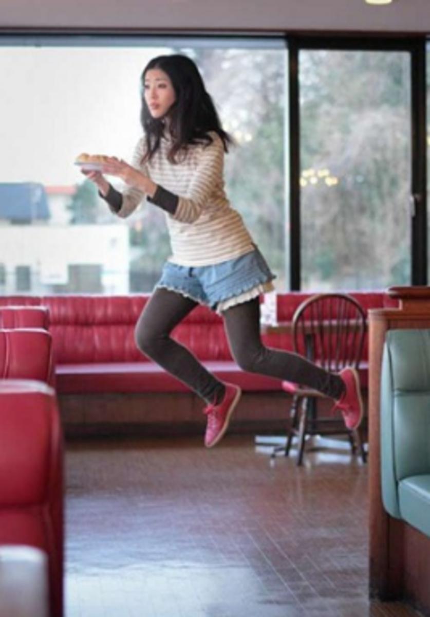 Asian girl levitating in restaurant.