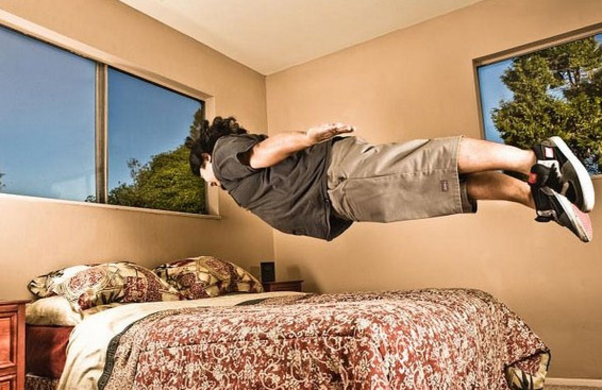 boy levitating over his bed in his bedroom