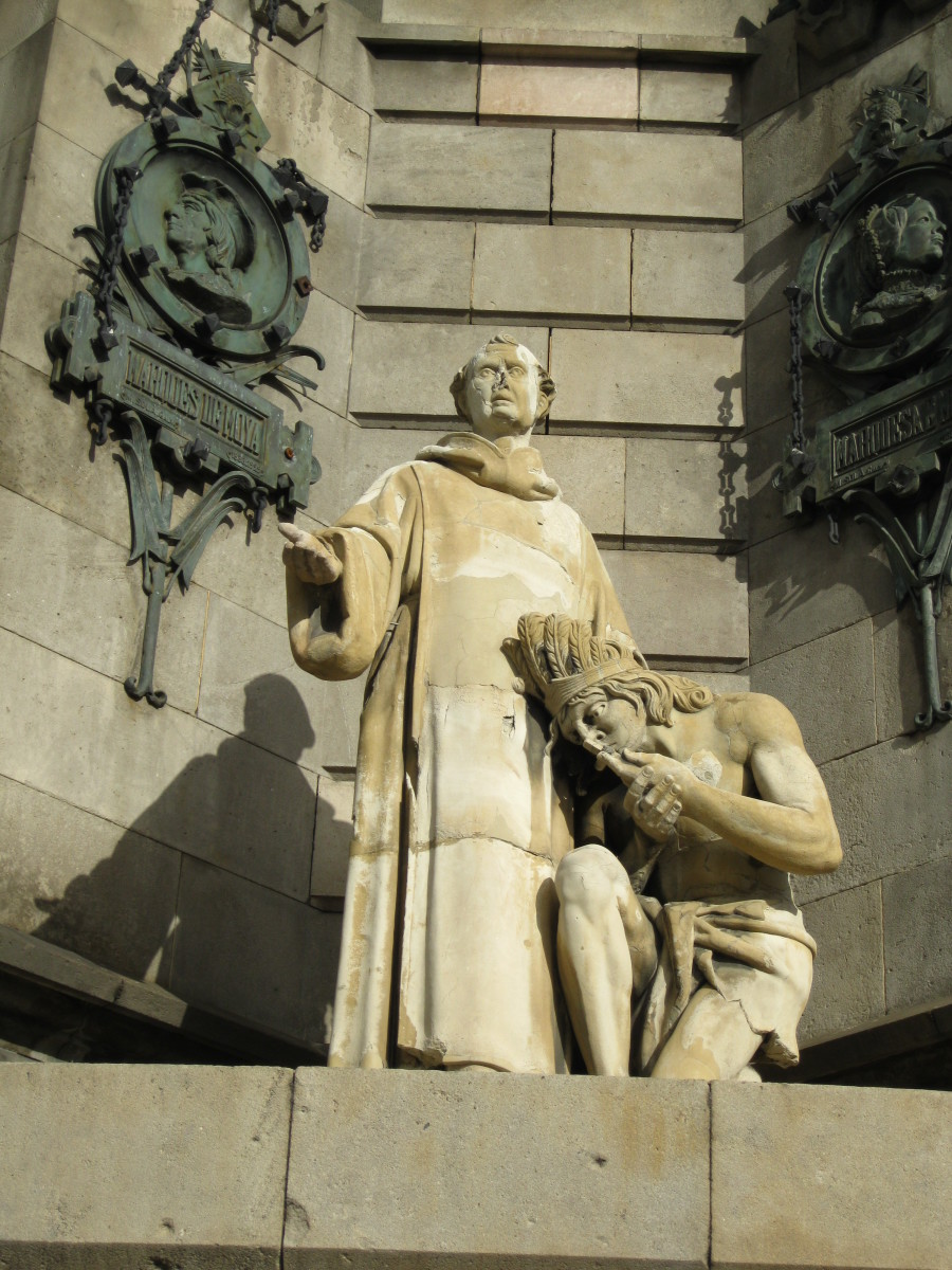 Priest with a kneeling Indian at base of Columbus Monument in Barcelona, Spain