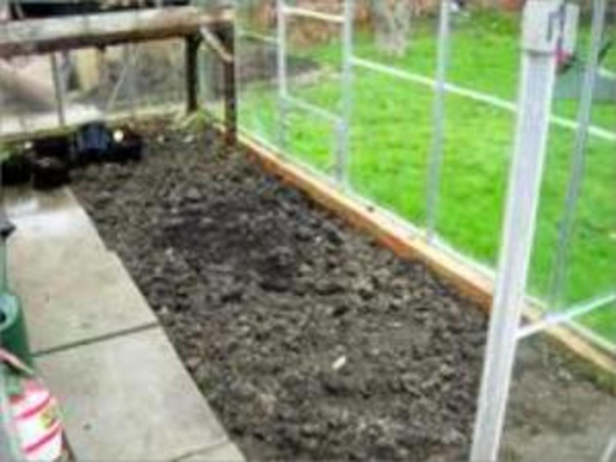 Border soil prepared for planting, pots or growing bags.