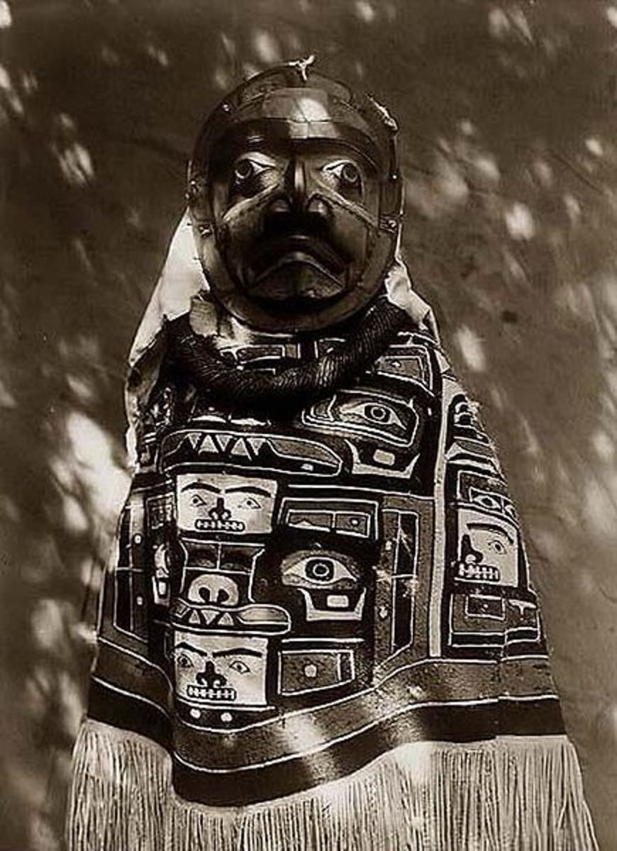 From Alaska, this is a woman in a fringed Chilkat blanket, a Hamatsa neck-ring and a mask representing a deceased relative who had been a shaman.