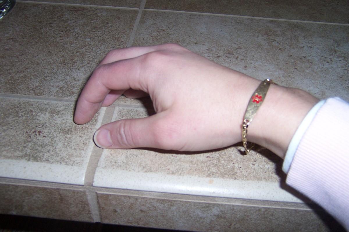 A subtle gold medic alertl bracelet with rod of Asclepius symbol