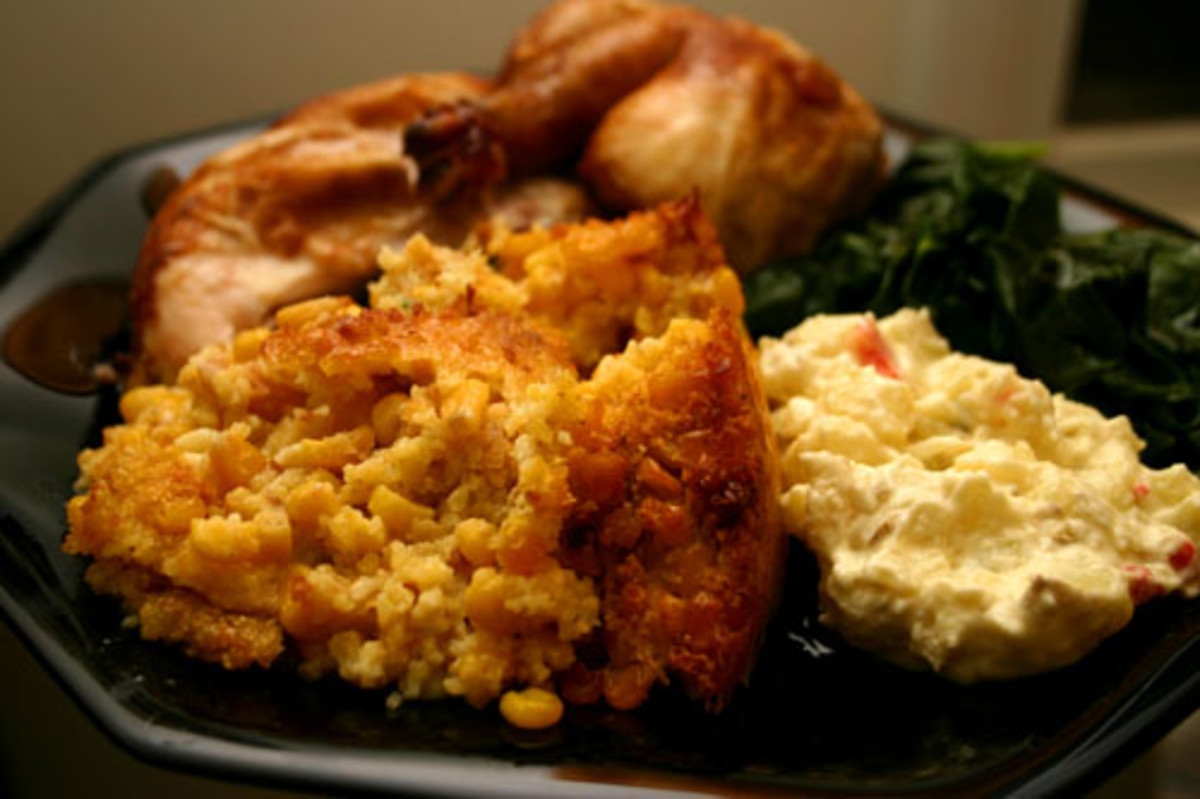 corn pudding served with chicken, greens, and potato salad
