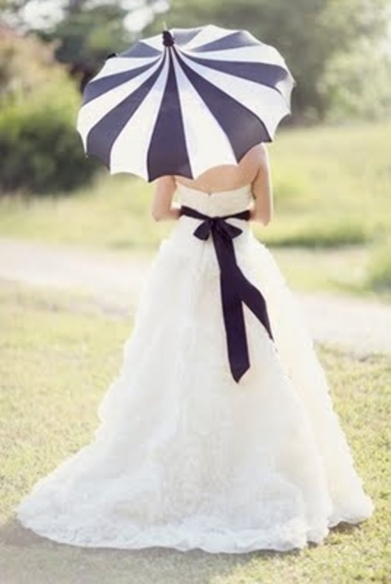 This black and white umbrella is the perfect accessory to match the bride's white gown with a black ribbon.