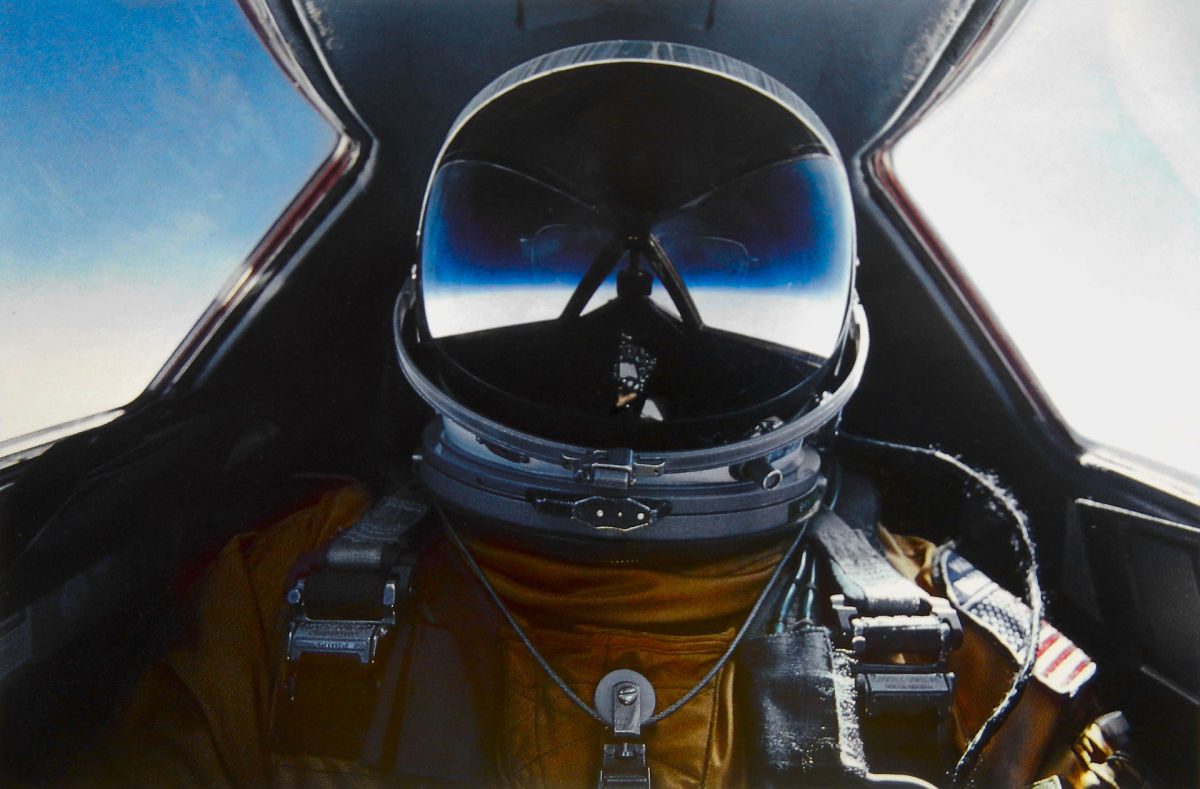 A SR-71 pilot in his pressurized suit whose helmet's visor captures the inky blackness of near space.