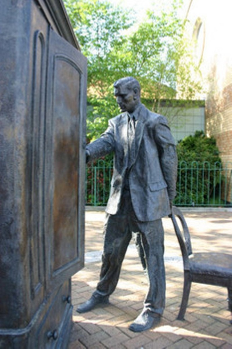 Statue of C.S. Lewis entering a wardrobe.