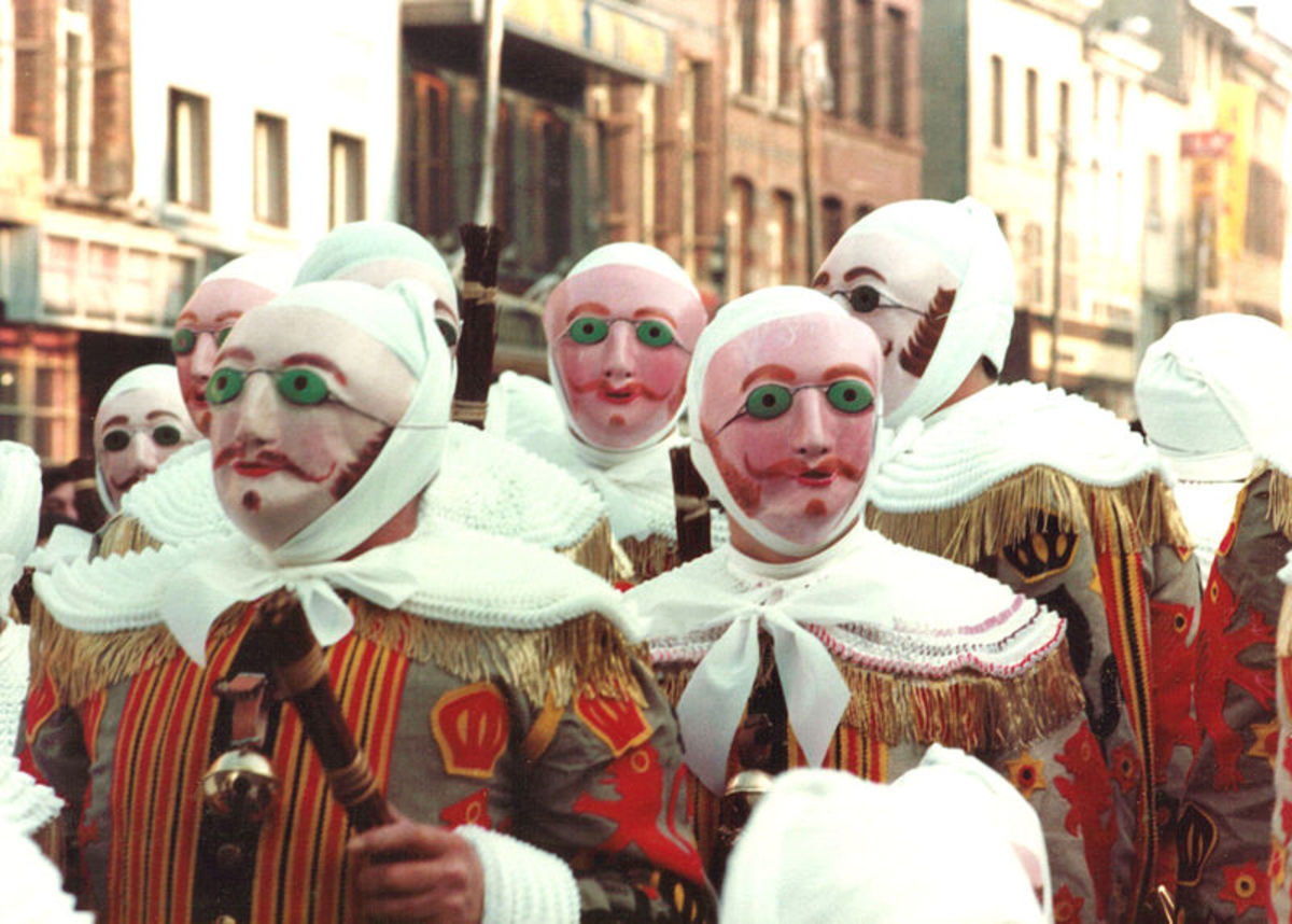 The Gilles use wax masks and hold wielding sticks to protect themselves against spirits