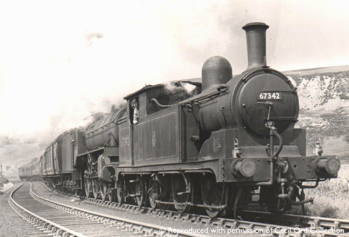 Darlington G5 67342 pilots an unknown Class B1 4-6-0 with a heavy Whitby-bound holiday express (two lamps on the pilot) over Goathland summit - she may have taken a train to Malton and been seconded to this duty to return to her home depot
