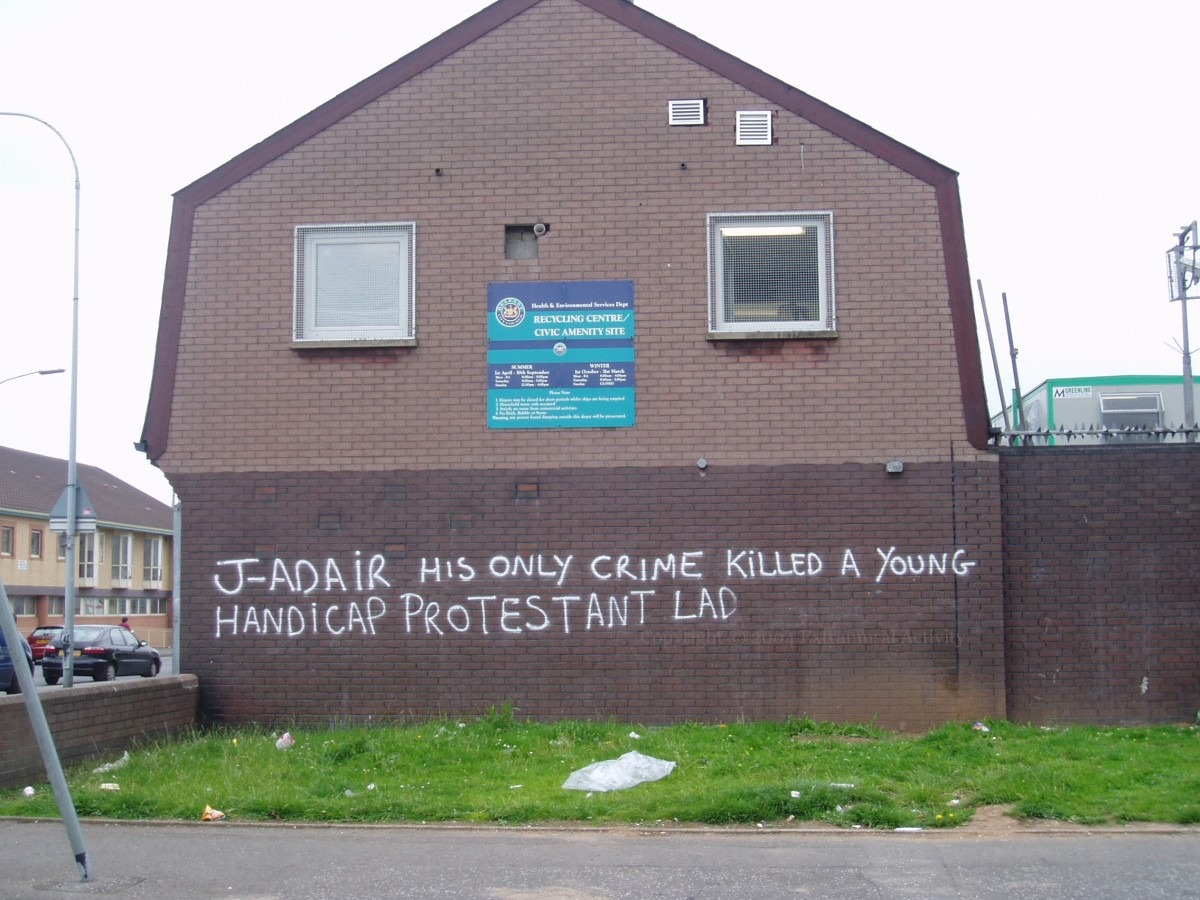 Anti-Johnny Adair graffiti in the UDA Lower Shankill, Belfast, after he was expelled in an intra-UDA feud.(Presumably if the disabled kid had been Catholic that would not have been seen as problematic?)