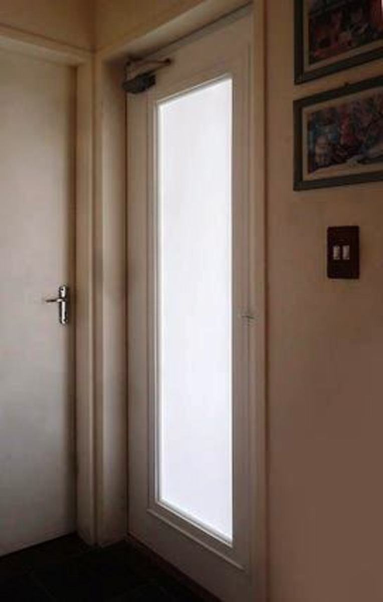 Here is a glass-fitted door that lets light flow from a natural source of light into a dark hallway.