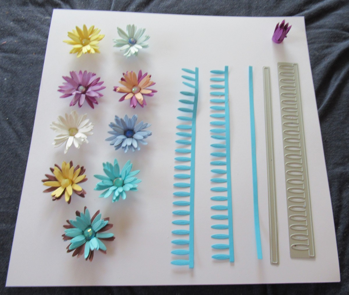Dies are easy to use for rolled flowers. You use a die machine to cut the die, Then you roll and glue the flowers together. Showing the die and the die cut. Upper right hand corner shows the flower after it is rolled, Then the final flower design/