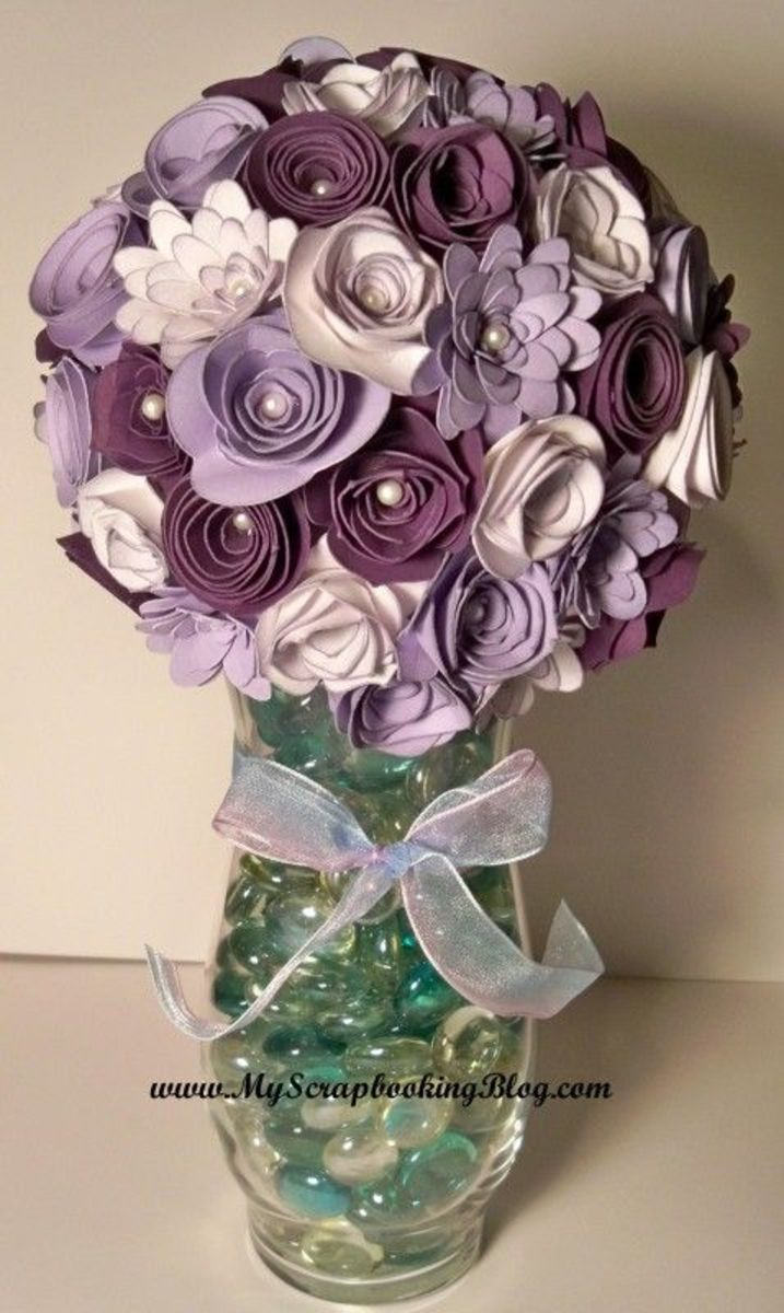 You can take a rolled flower and make an arrangement for your home or as a gift. Simply bend a floral wire and hot glue the flower to the stem. Wrap it in floral wire, Add paper or silk leaves. Arrange in a vase or a container.