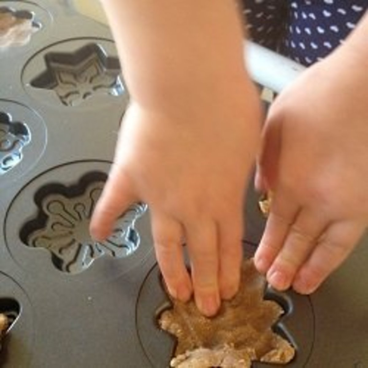 Our four-year-old granddaughter pressing dough snowflakes into the cookie molds
