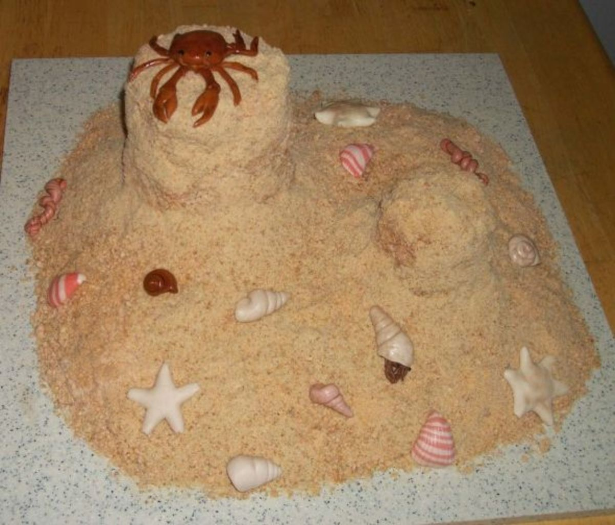 Sandcastle beach cake with hermit crabs, starfish, and seashells