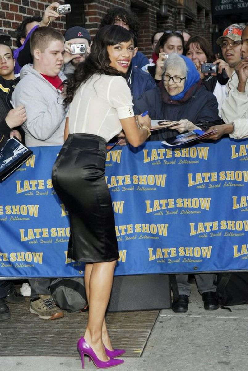 Rosario Dawson greeting her fans in a black pencil skirt and purple pumps