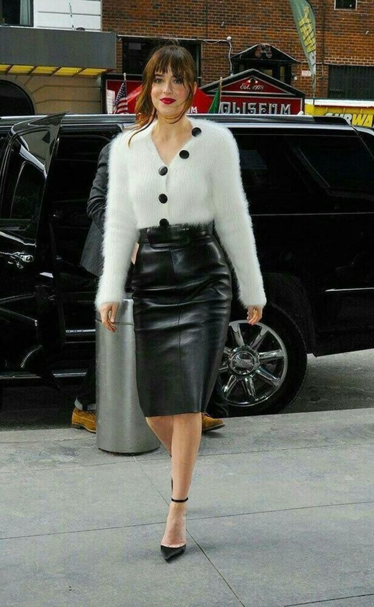 Dakota Johnson in a fuzzy white sweater and black leather pencil skirt with high heels