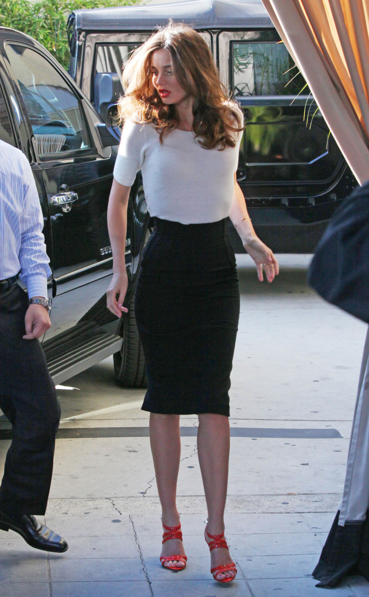 Miranda Kerr is a sexy black pencil skirt, white top and cute stappy high heels.