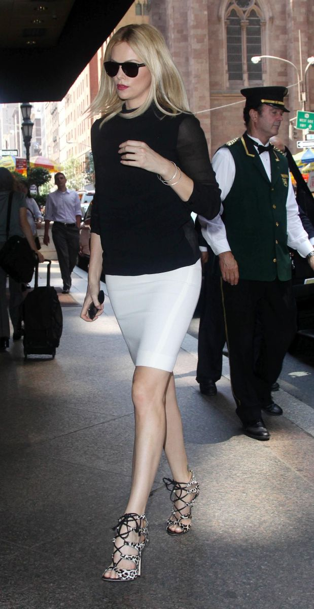 Charlize Theron in a white pencil skirt and strappy heels entering The View