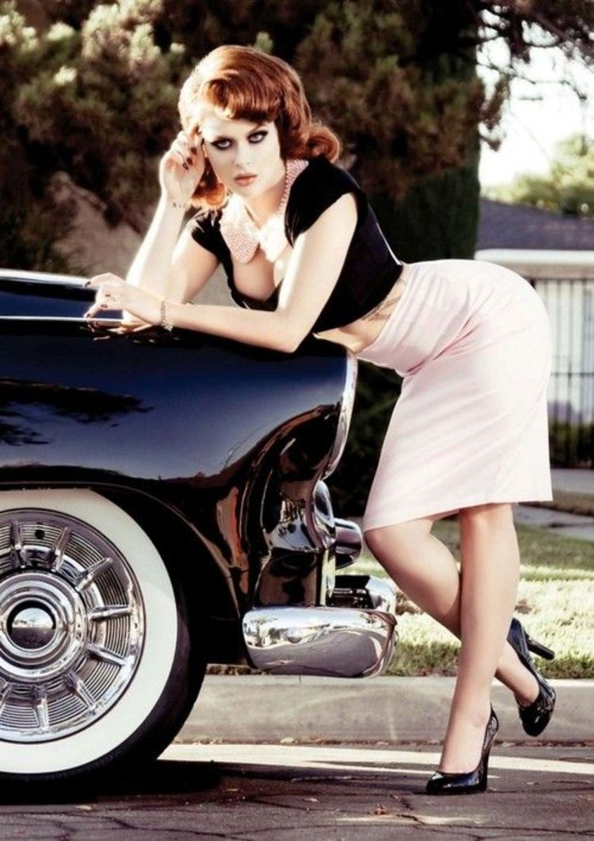 Renee Olstead in a white pencil skirt and shiny black pumps posing with a classic car
