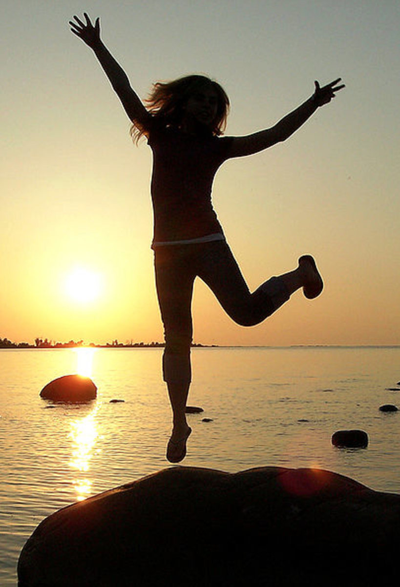 Silohuette of girl leaping/hopping at sunset.