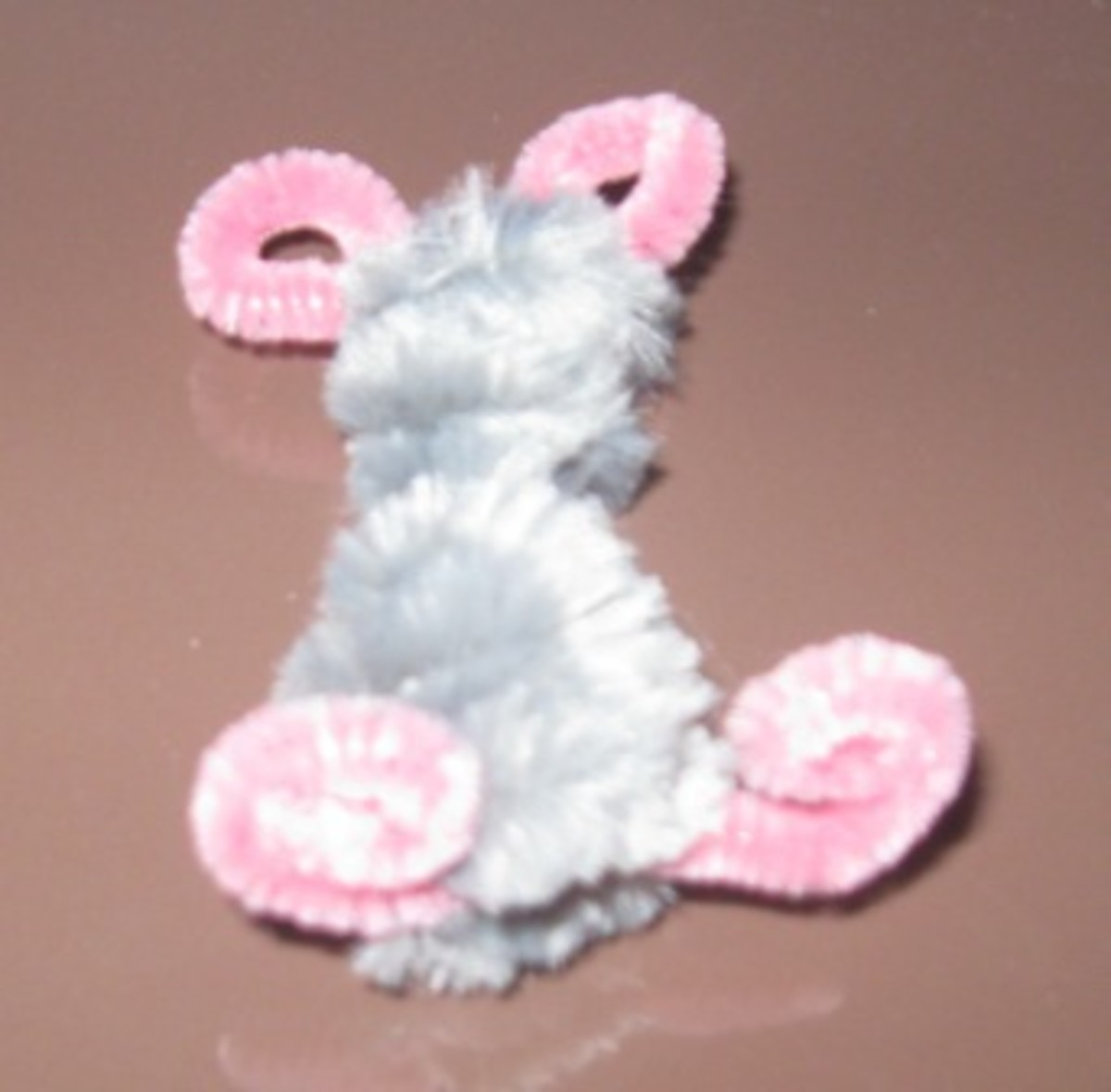 4. Push the center of the pink pipe cleaner down and shape around a pencil to form the mouses ears.