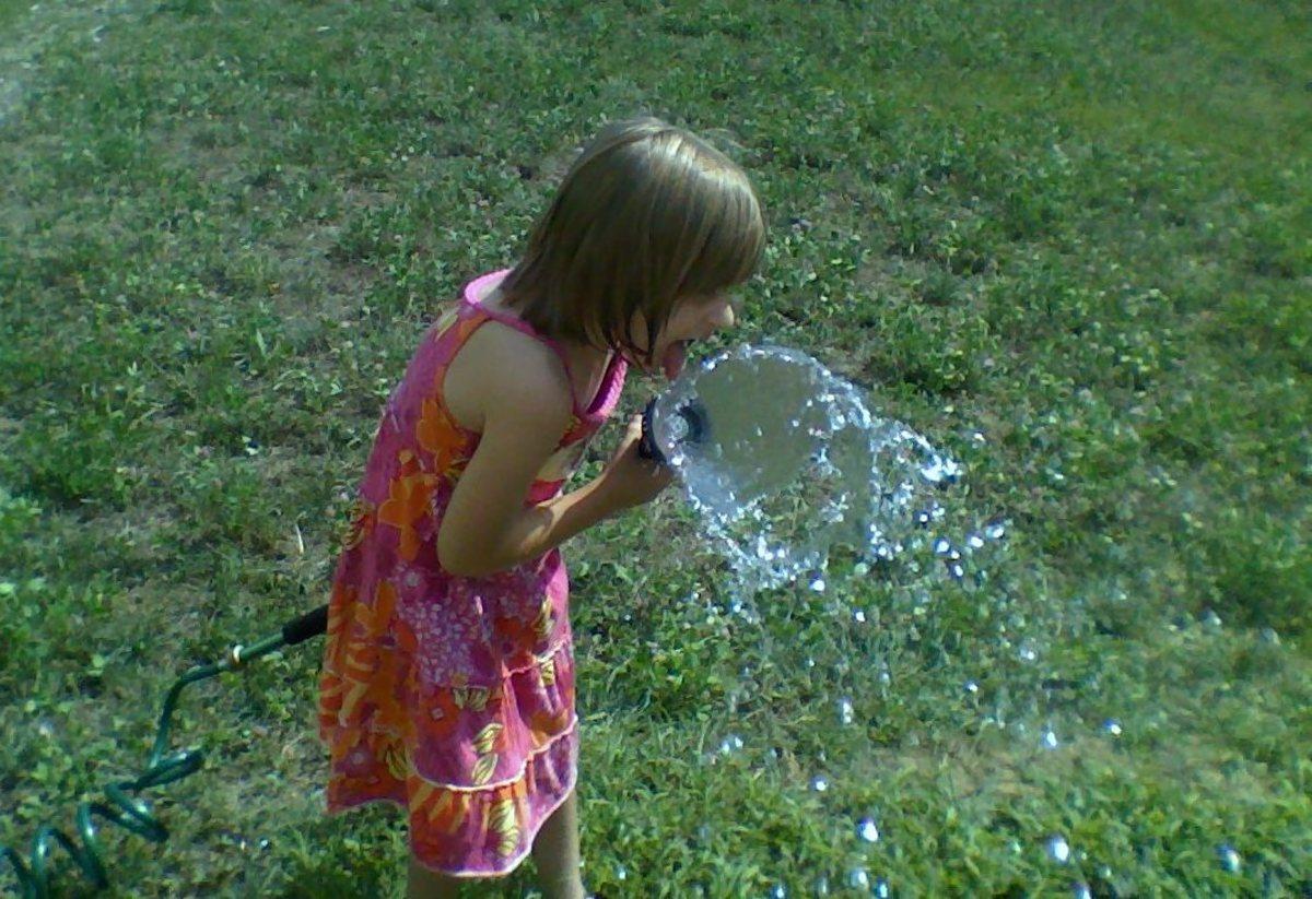 Delighting in a refreshing drink of water before watering Mama's backyard garden