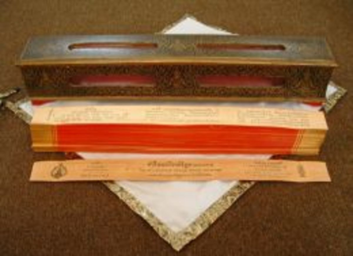 In ancient times the Pali Canon was written on thin slices of wood. The 'pages' are kept on top of each other by two thin sticks, which go through little holes in the scripture. The scripture is wrapped in cloth and stored inside the box Click thumbn