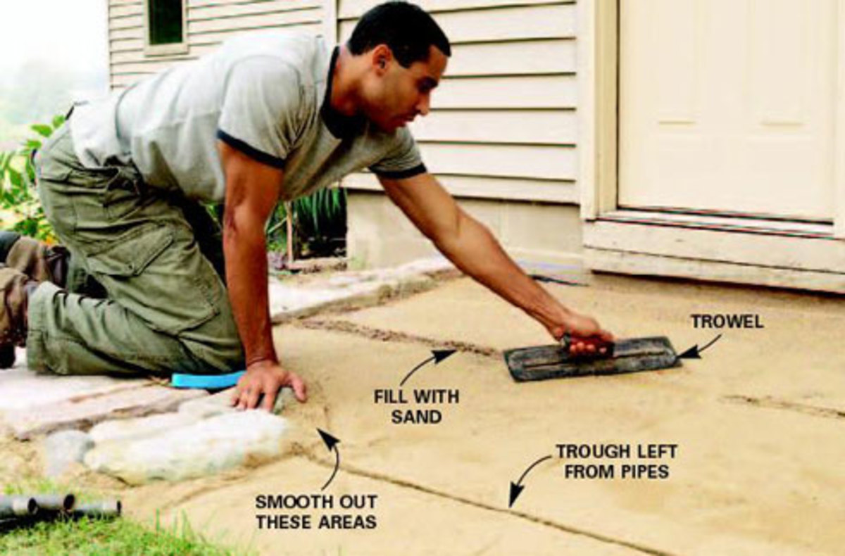 Smoothing the sand bed with a hand trowel