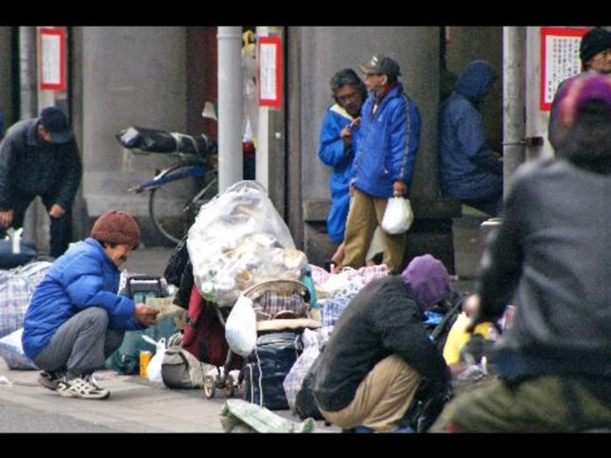 A stream of homeless men arriving at  the area's largest shelter in Airin's dirt covered park; these men with greying hair and thick coats warming themselves, around a fire as others rummaged through the piles of trash, in Japan.