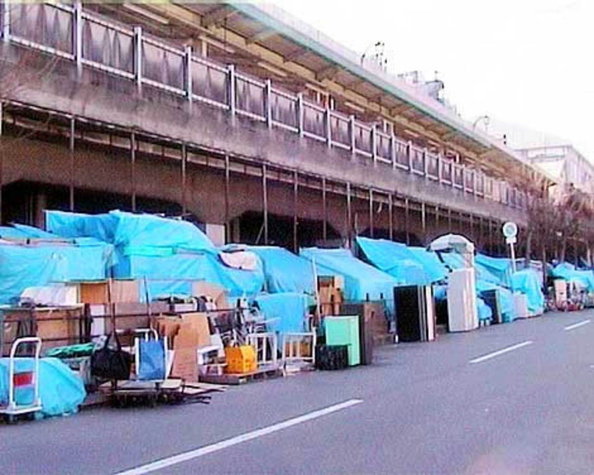 Homeless in Osaka, Japan. There are about 25,000 people homeless in Osaka. The entrance of the area's largest shelter, with 20-foot pale green metal walls dominating the park