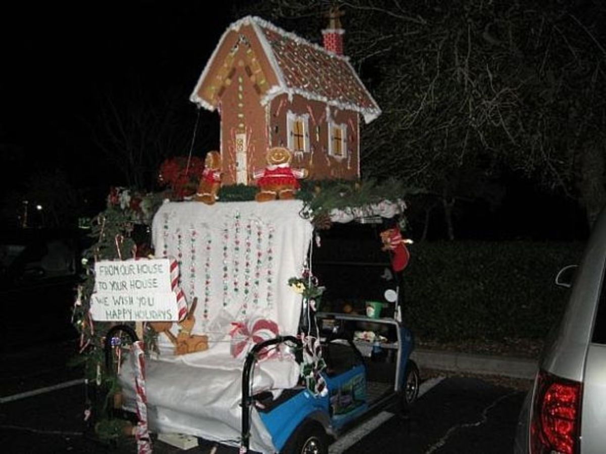 Golf cart, ready for the Christmas parade, with a gingerbread house on it.