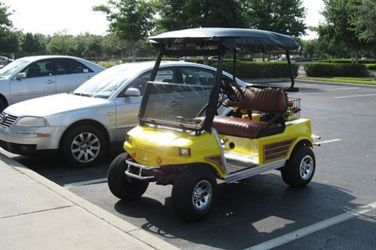 "Yellow golf cart with ""woodie"" sides."