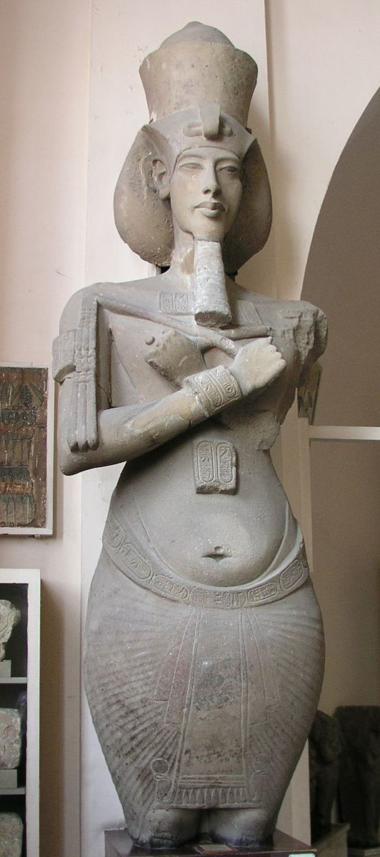 Akhenaton in a typical El Amarna Art style. His face is long and narrow, his shoulders narrow and hips wide.. Many see a feminine form in his body, but it's not known if this was an expression for a fruitful sun, and whether his body was like this.