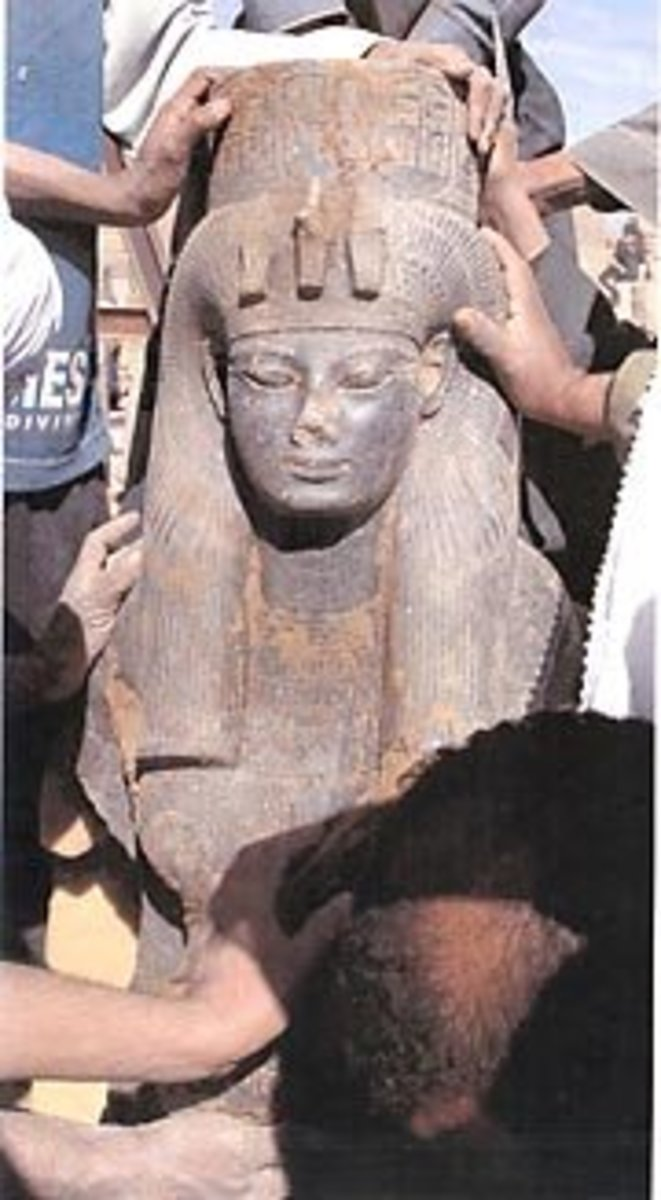 Black granite statue of Queen Tiye, mother of Akhenaton. This statue features a standing Queen Tiye wearing a wig and a cobra-decorated crown.