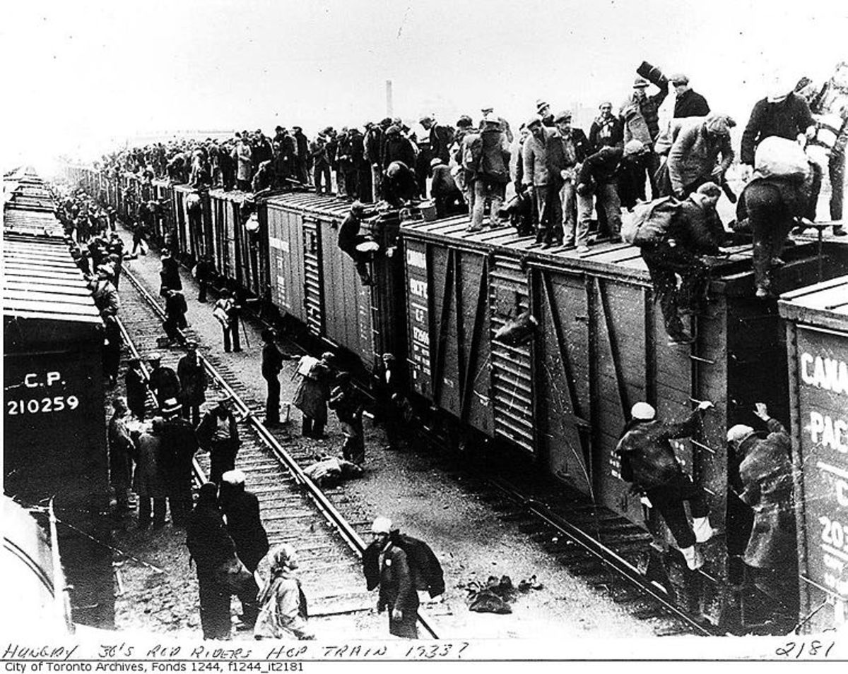 On to the next camp! Men board a freight train, including the roof, in order to find another work camp.