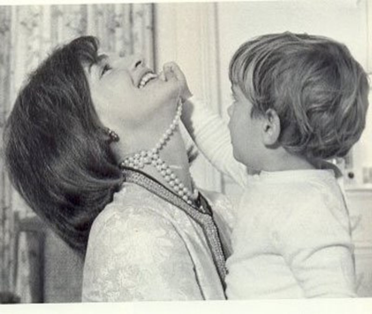 photo of Jackie Kennedy wearing her famous three strand pearl necklace with JFK Jr playing with the necklace