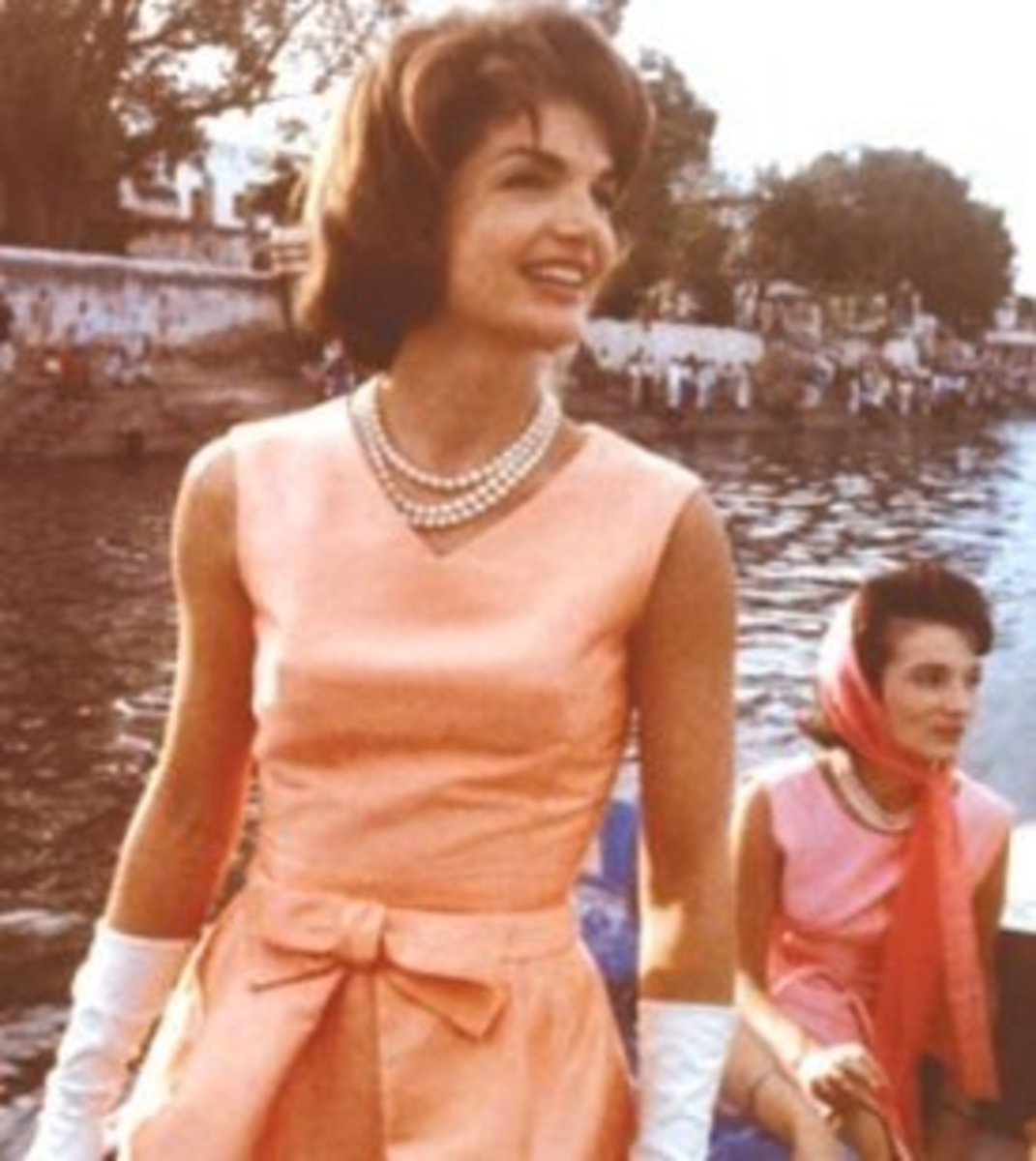 Jackie Kennedy wearing her three strand pearl necklace with her sister Lee in the background