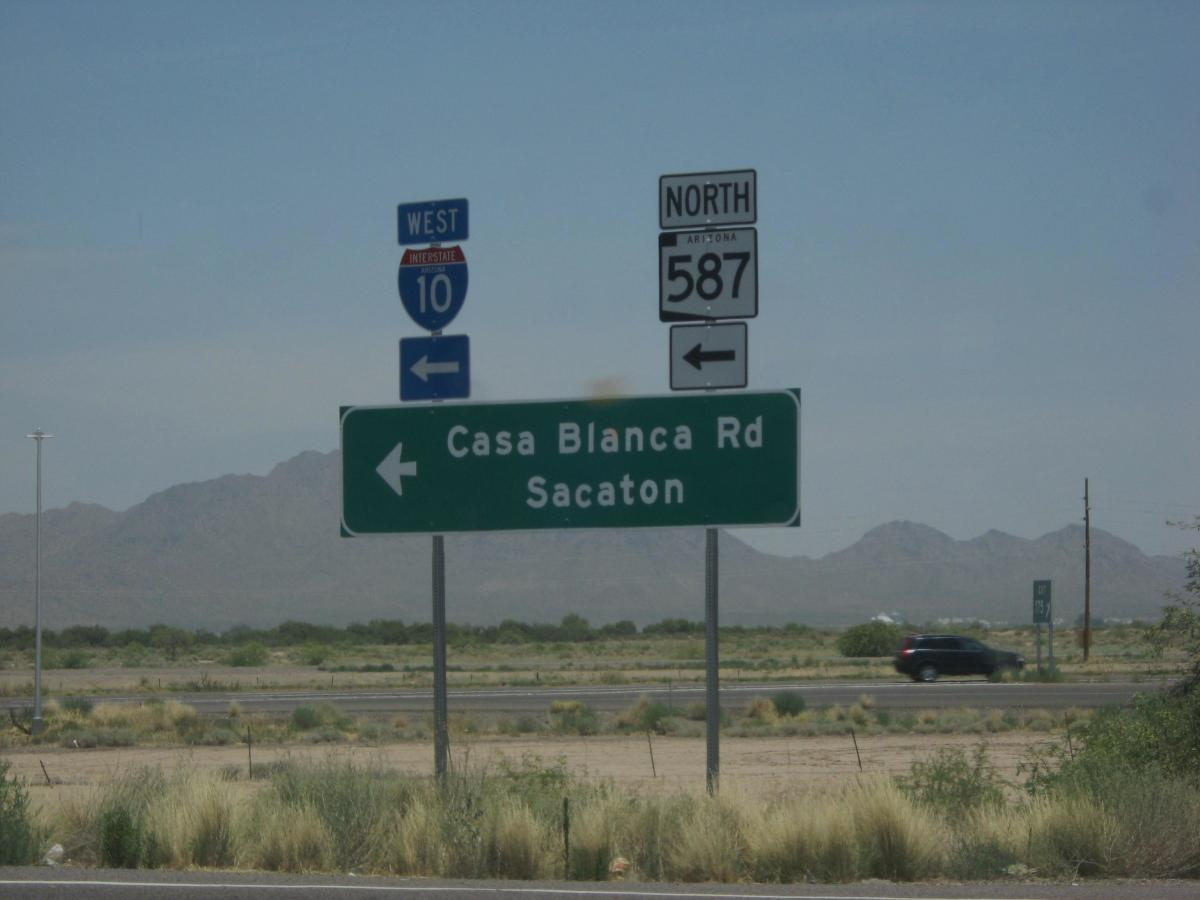 Sign in Arizona desert pointing way to city of Sacaton, Arizona