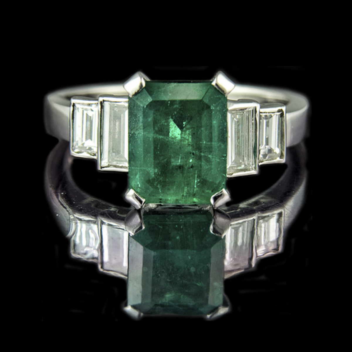 "Emerald engagement ring. Stone is also ""emerald cut"" as are side diamonds."