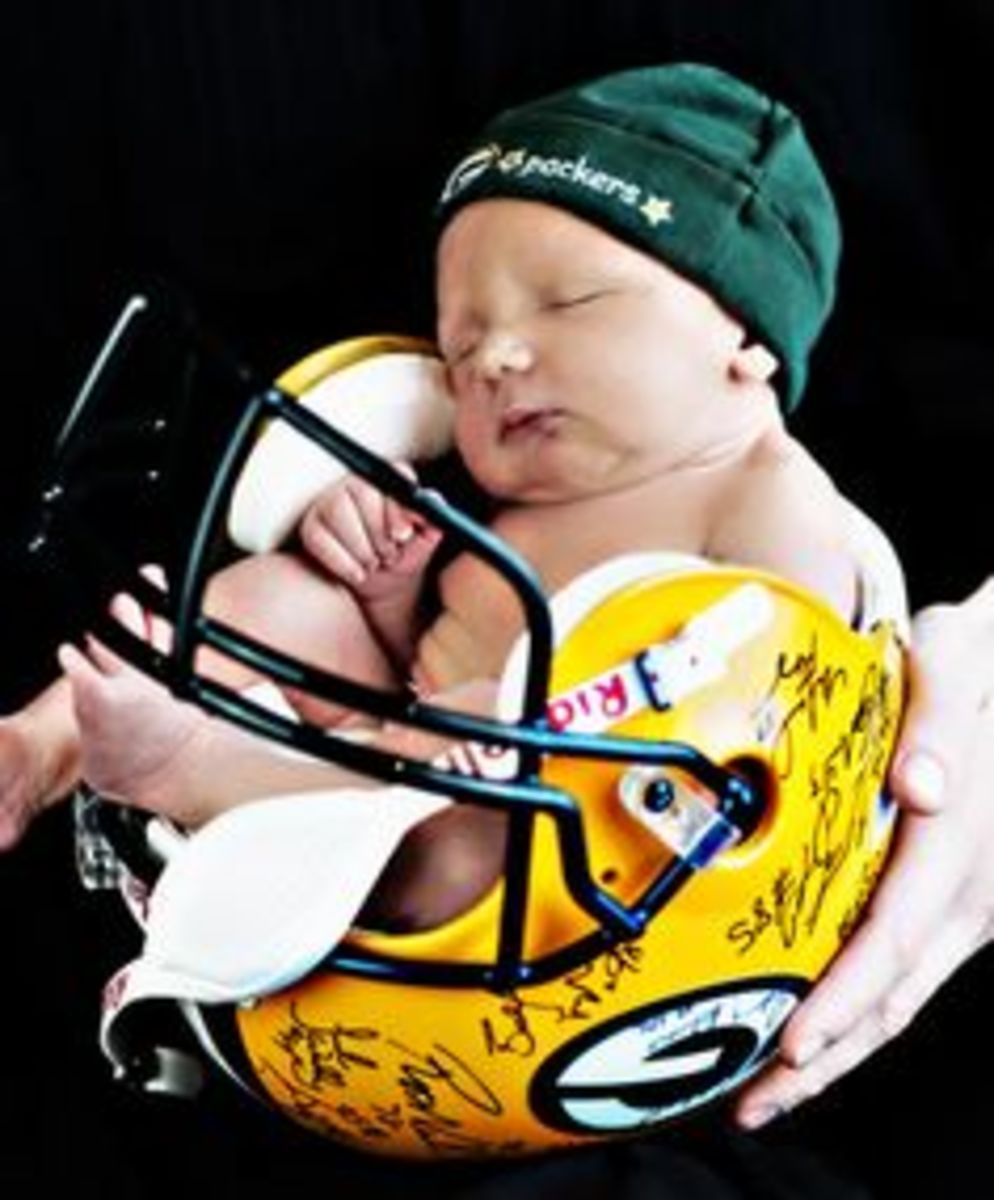 Sports Themed Gift Giving Ideas - photo of baby held in a Green Bay Packers helmet as a cradle wearing a Green Bay Packers bonnet