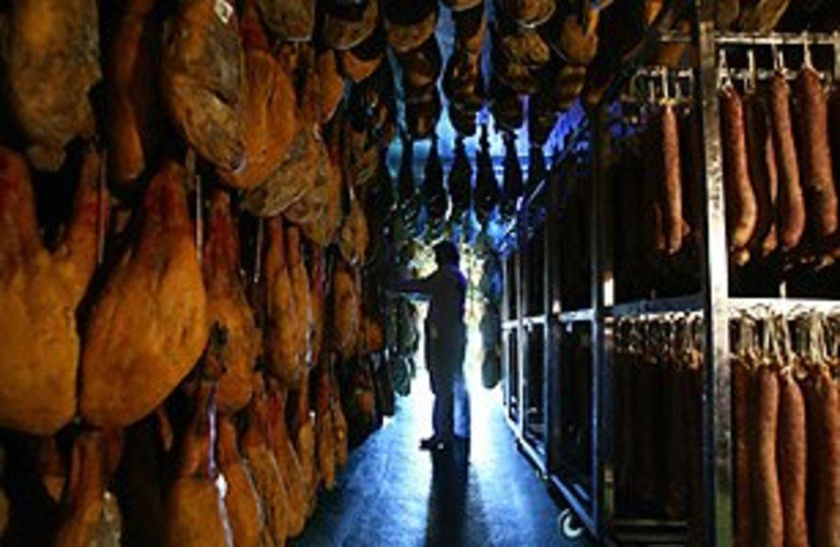 Man checks hams in drying room