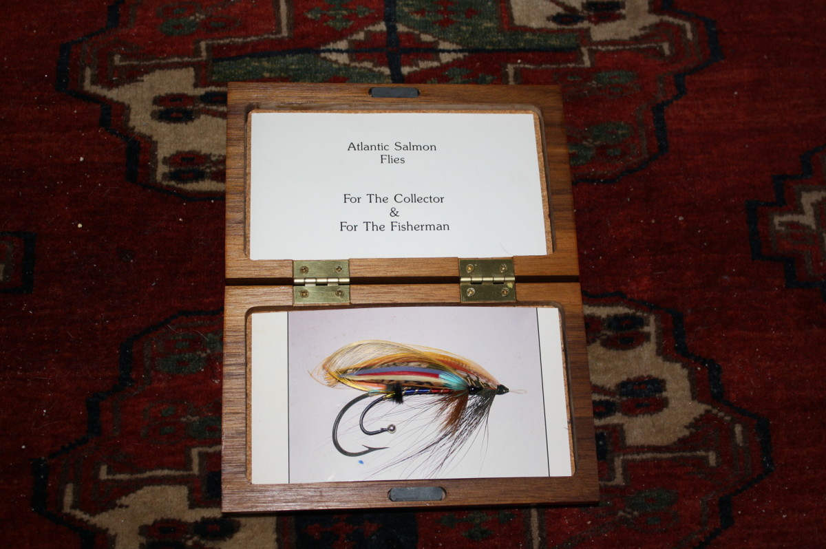 "This photo is of my salmon fly, 'The Jewel' , in a fancy hardwood box. The fly is superimposed over a photo of a ""Black Dog"" which appeared on the cover of my 1986 salmon fly bookalog"