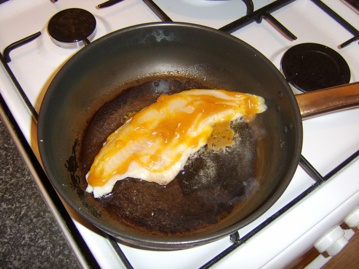 The curry sauce is spread evenly over the flesh side of the coley fillet