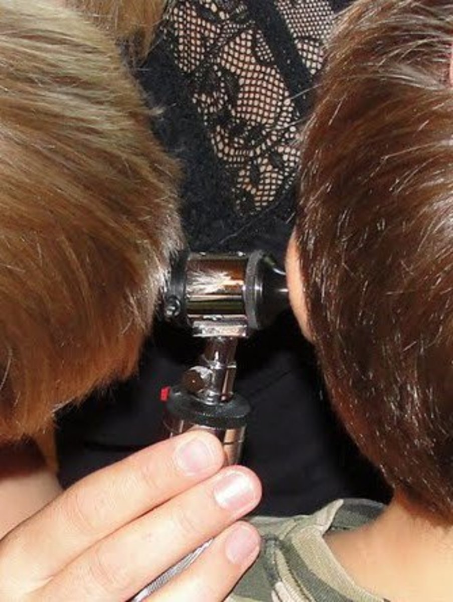 Looking into a child's ear using an otoscope