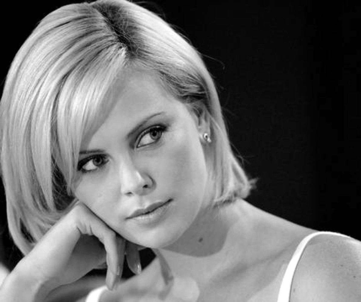 Charlize Theron has a straight medium hair style cut to sit right at the jawline with long jagged bangs combed to the side.